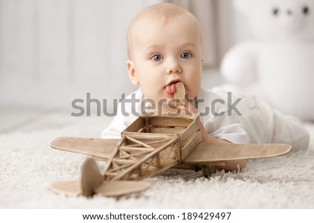Portrait of a baby with the airplane on the carpet in my room - stock photo