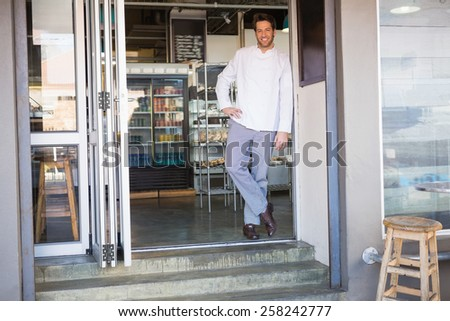 Portrait of a baker posing and smiling at the bakery - stock photo