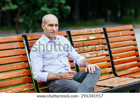 Portrait of a bald and brutal man. Bald man sitting on a bench in the park - stock photo