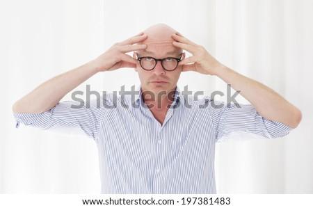 portrait of a bald man with a headache - stock photo