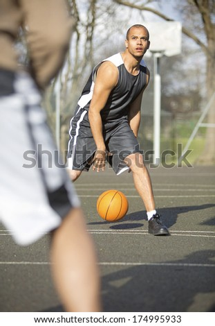 Portrait of a Basketball game of one on one with the ball handler looking at the hoop with a  determined look on his face as he dribbles the ball - stock photo