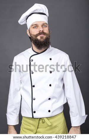 Portrait of a bearded young chef over gray background - stock photo