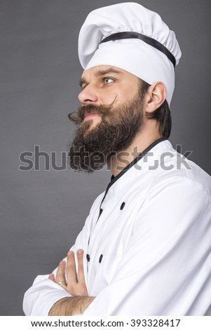 Portrait of a bearded young chef with arms folded over gray background - stock photo