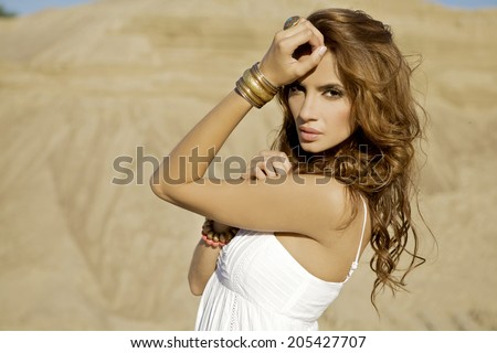 portrait of a beautiful adult sensuality and attractive woman in sand background desert - stock photo