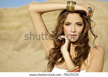 portrait of a beautiful adult sensuality woman on blue sky and sand background - stock photo