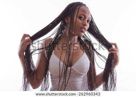 portrait of a beautiful African woman whith braids in a seductive dress posing on an isolated background - stock photo