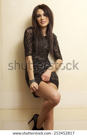 Portrait of a beautiful and attractive young adult sensuality female pretty brunette woman posing in black elegance dress in luxury style apartment - stock photo