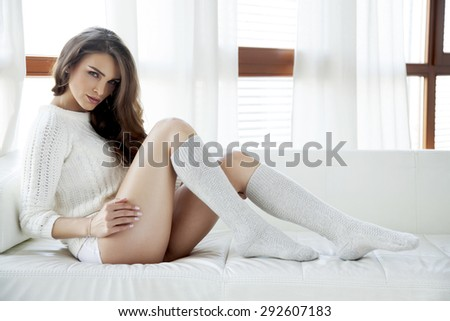 Portrait of a beautiful and sexy young adult sensuality attractive pretty brunette woman in white sweater and grey socks on the white sofa in morning sunlight  window on luxury  style hotel apartment - stock photo