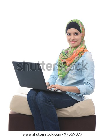 Portrait of a beautiful asian muslim woman smiling to the camera while using laptop - stock photo
