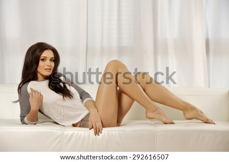 Portrait of a beautiful attractive sexy and sensuality young adult pretty blonde woman long legs in grey sweater on the white couch - stock photo