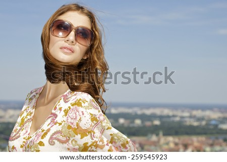 portrait of a beautiful attractive young adult sensuality and sexy pretty brunette woman in sunglasses on background blue sunlight sky - stock photo