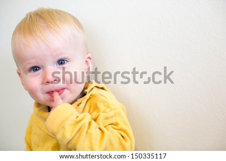 Portrait of a beautiful baby boy with blond hair and blue eyes. - stock photo