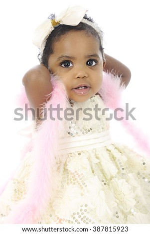 Portrait of a beautiful baby girl all dressed up in a white hair bow, sequin dress and pink boa.  On a white background. - stock photo