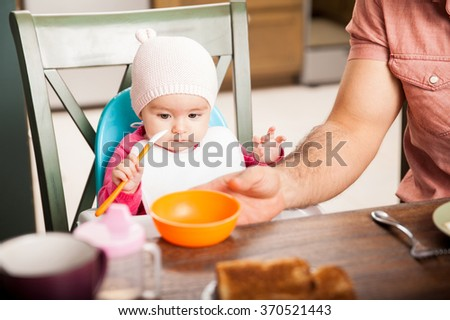 Portrait of a beautiful baby girl trying to eat by herself next to her dad - stock photo