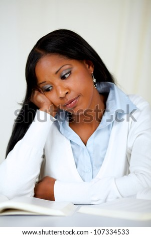 Portrait of a beautiful black tired woman learning at soft colors composition - stock photo