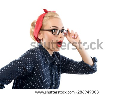 Portrait of a beautiful blond pin up girl with ponytail and red bandana wearing a blue dotted dress touching her glasses looking very surprised, side view, isolated on white background - stock photo