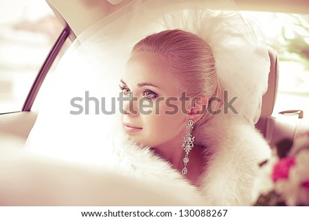 Portrait of a beautiful blonde bride sitting in the wedding car and looking at somebody or something through the window. Wedding day. Daylight - stock photo