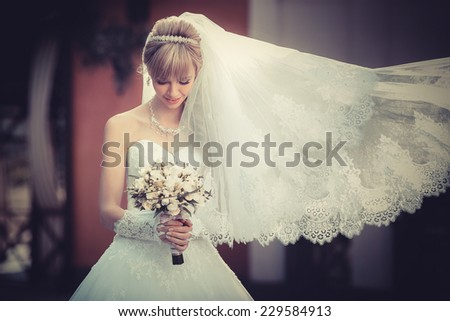 Portrait of a beautiful blonde bride with wedding bouqet in the hands - stock photo