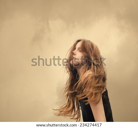 portrait of a beautiful blonde carefree on a windy day - stock photo