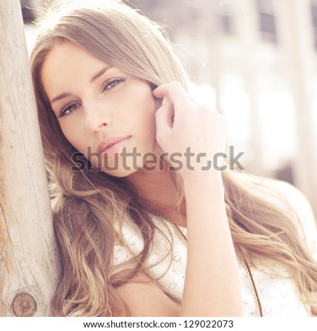portrait of a beautiful blonde close-up in sunny weather. pictures in warm colors - stock photo