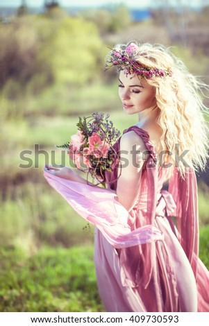 Portrait of a beautiful blonde girl in a pink dress with long developing a bouquet of flowers in their hands - stock photo