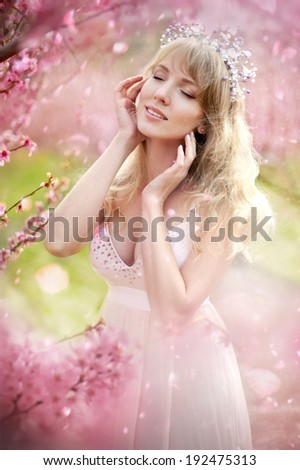 portrait of a beautiful blonde girl in the flowered garden - stock photo