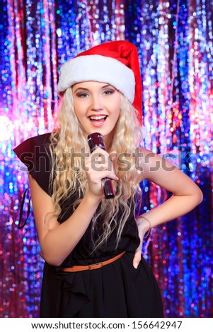 Portrait of a beautiful blonde girl singing with a microphone. Disco lights in the background. - stock photo