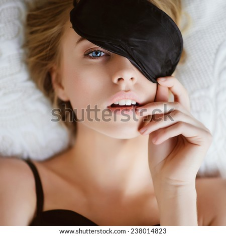 Portrait of a beautiful blonde girl with a mask for sleeping, lifestyle - stock photo