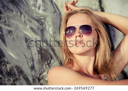 portrait of a beautiful blonde girl with sunglasses sitting near the wall at the day time - stock photo
