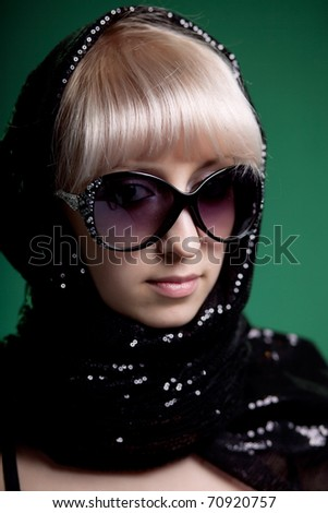 portrait of a beautiful blonde in a dark scarf and sunglasses - stock photo