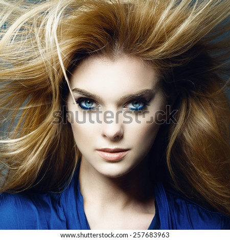 Portrait of a beautiful blonde woman in studio on a blue background with developing hair, the concept of health and beauty - stock photo