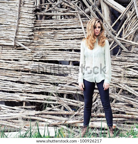 Portrait of a beautiful blonde woman standing by a old wall - stock photo