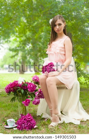 Portrait of a beautiful blonde woman with peony flowers. Fashion photo - stock photo