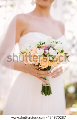 Portrait of a beautiful bride outdoors. Beautiful women in a wedding dress. Wedding bridal bouquet. The bride holds a fine wedding bouquet in hand. - stock photo