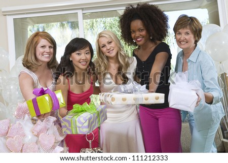 Portrait of a beautiful bride with her friends and mother holding gifts at  party - stock photo