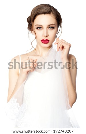 Portrait of a beautiful bride with red lips, she is holding a veil in her hands. - stock photo