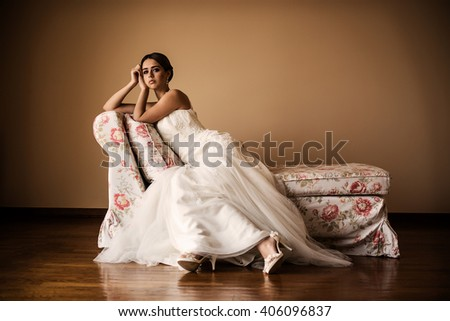 Portrait of a beautiful brunette bride sitting on a sofa - stock photo