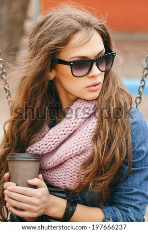 Portrait of a beautiful brunette girl in sunglasses holding drink in her hands, in park. Warm sunny day. Outdoors - stock photo