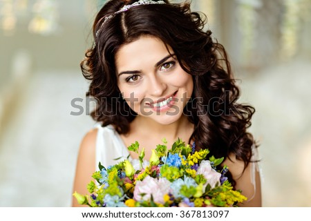 Portrait of a beautiful brunette girl in white dress with charming toothy smile and a bouquet of wildflowers on a background of bright interiors - stock photo