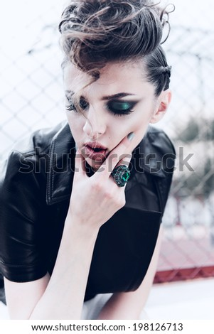 Portrait of a beautiful brunette girl with a mohawk, rock style, outdoors - stock photo