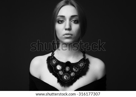 portrait of a beautiful brunette girl with handmade jewelry accessories - stock photo