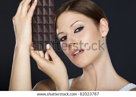 Portrait of a beautiful brunette holding a chocolate bar in both hands - stock photo