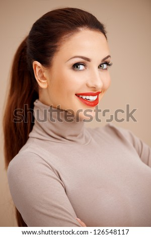 Portrait of a beautiful brunette  smiling and looking at camera - stock photo