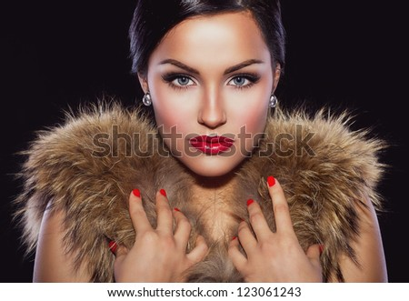 Portrait of a beautiful brunette with classic make up and red lips, holding her hands on fur - stock photo