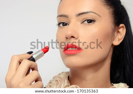 Portrait of a beautiful brunette woman applying red lipstick on her lips. Woman holding with her hand with black fingernails a red lipstick - stock photo