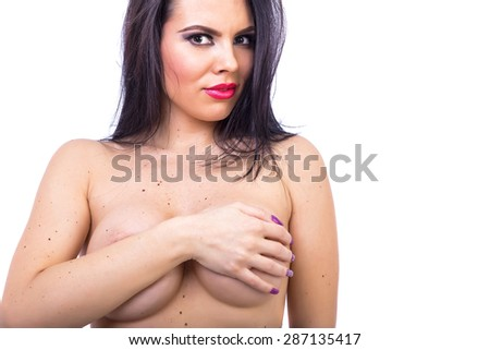 Portrait of a beautiful brunette woman covering her breasts against white background - stock photo