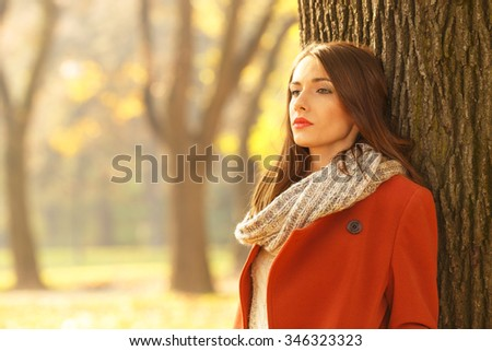 Portrait of a beautiful brunette woman in autumn park. She is looking into the distance. - stock photo