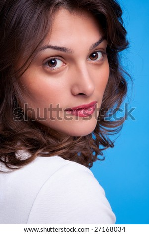 Portrait of a beautiful brunette woman looking over her shoulder, blue background. - stock photo