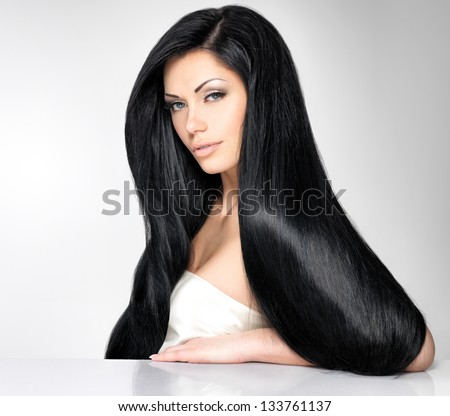 Portrait of a beautiful brunette woman with long straight hair poses at grey background - stock photo