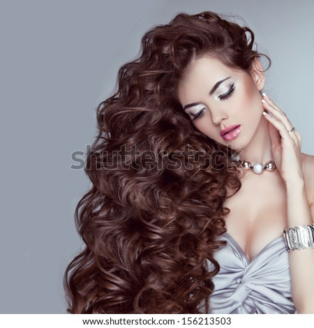 Portrait of a beautiful brunette woman with long wavy hair poses at grey background - stock photo